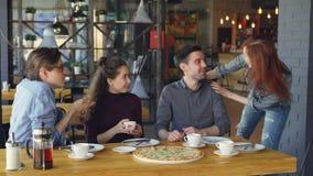 A moça bonita está encontrando seus amigos na casa da pizza que faz a elevação cinco e que fala aos companheiros que bebem o chá  filme