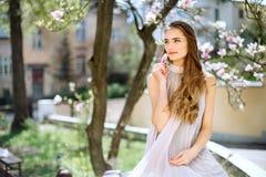 A moça bonita está entre as árvores de florescência Flores brancas Menina da mola com seu cabelo em um vestido bege foto de stock royalty free