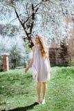 A moça bonita está entre as árvores de florescência Flores brancas Menina da mola com seu cabelo em um vestido bege fotografia de stock royalty free
