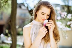 A moça bonita está entre as árvores de florescência Flores brancas Menina da mola com seu cabelo em um vestido bege fotos de stock