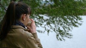 A moça bonita está na terraplenagem do rio e do copo bebendo do café afastado do copo descartável vídeos de arquivo