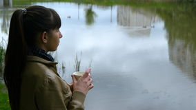 A moça bonita está na terraplenagem do rio e do copo bebendo do café afastado do copo descartável video estoque