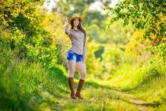 A moça bonita está sentando-se na grama no jardim Imagens de Stock