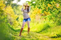 A moça bonita está sentando-se na grama no jardim Imagem de Stock