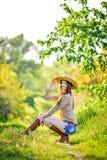 A moça bonita está sentando-se na grama no jardim Fotos de Stock