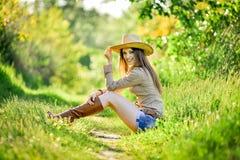 A moça bonita está sentando-se na grama no jardim Fotografia de Stock