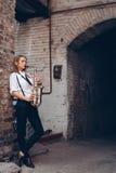 A moça bonita joga um saxofone que está perto de uma parede velha branca - fora Mulher atrativa nos jogos brancos da expressão da Imagem de Stock Royalty Free