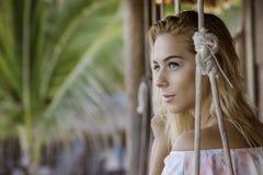 Moça bonita loura que senta-se em um balanço da corda fotos de stock royalty free