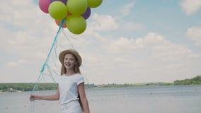 A moça bonita mostra emoções felizes com balões à disposição no coustline video estoque