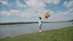 A moça bonita mostra emoções felizes com balões à disposição no coustline vídeos de arquivo