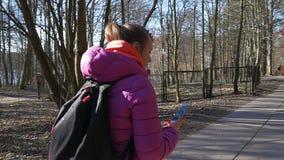 A moça bonita nas madeiras olha mapas do telefone e toca no cabelo Roupa cor-de-rosa, floresta da mola, movimento lento video estoque