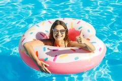 Moça bonita no biquini com círculo cor-de-rosa inflável da filhós na piscina azul imagem de stock