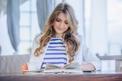Moça bonita no café exterior a de leitura fotografia de stock