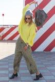 A moça bonita no moderno veste-se, óculos de sol, chapéu, dançando com uma trouxa no fundo de uma parede com listras Imagens de Stock