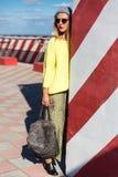 A moça bonita no moderno veste-se, óculos de sol, chapéu, estando com uma trouxa no fundo de uma parede com listras Foto de Stock