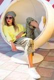 A moça bonita no moderno veste-se, óculos de sol, chapéu que descansa em uma cadeira redonda Imagem de Stock