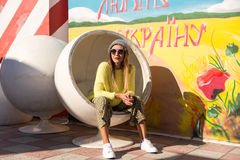 A moça bonita no moderno veste-se, óculos de sol, chapéu que descansa em uma cadeira redonda Imagens de Stock