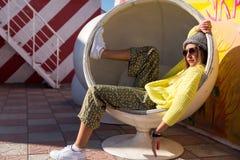 A moça bonita no moderno veste-se, óculos de sol, chapéu que descansa em uma cadeira redonda Fotografia de Stock Royalty Free