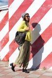 A moça bonita no moderno veste-se, óculos de sol, chapéu, steping com uma trouxa no fundo de uma parede com listras Foto de Stock Royalty Free