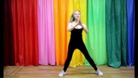 A moça bonita no sportswear que faz a dança simples move-se vídeos de arquivo