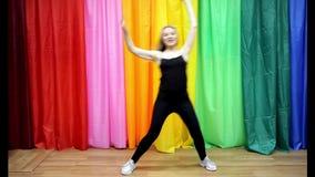 A moça bonita no sportswear que faz a dança simples move-se filme
