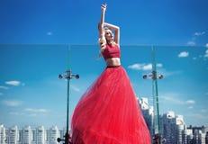 Moça bonita no telhado de uma construção em um vestido luxúria vermelho fotos de stock