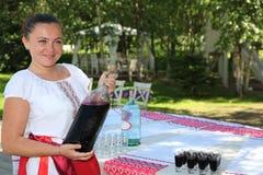 A moça bonita no traje ucraniano nacional apresenta a bebida alcoólica nacional Fotos de Stock