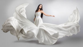 Moça bonita no vestido branco de voo Tela de fluxo Voo branco claro de pano imagem de stock