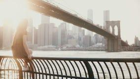 Moça bonita nos óculos de sol que sentam-se na cerca da terraplenagem do rio perto da ponte de Brooklyn, New York, apreciando a v filme