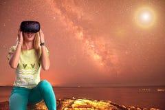 A moça bonita olha nos vidros da realidade virtual, cósmicos Fotografia de Stock Royalty Free