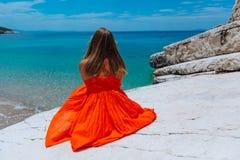Moça bonita pelo mar Mulher em um vestido vermelho na praia Férias do beira-mar Terreno rochoso fotos de stock