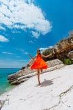 Moça bonita pelo mar Mulher em um vestido vermelho na praia Férias do beira-mar Terreno rochoso fotografia de stock royalty free