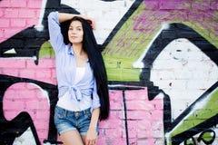 Moça bonita perto de uma parede com grafittis imagem de stock