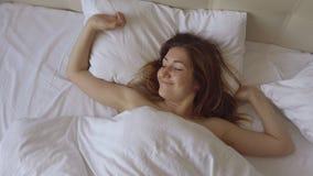 A moça bonita positiva acorda na cama grande e em olhar a câmera vídeos de arquivo