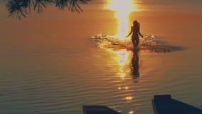 Moça bonita que corre na água contra vídeos de arquivo