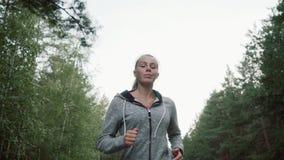 Moça bonita que corre no parque O louro é contratado no atletismo video estoque