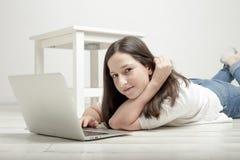 Moça bonita que encontra-se no assoalho com um portátil e um smilin fotografia de stock