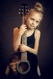 Moça bonita que está e que guarda uma guitarra Fotografia de Stock