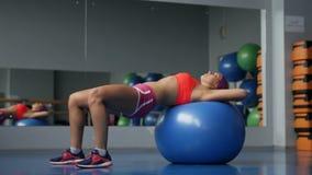Moça bonita que faz exercícios com a bola do ajuste no gym do esporte video estoque
