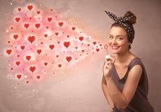Moça bonita que funde símbolos vermelhos do coração Imagem de Stock Royalty Free