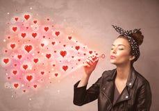 Moça bonita que funde símbolos vermelhos do coração foto de stock royalty free