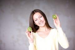 Moça bonita que guarda o quivi Alimento saudável Imagens de Stock Royalty Free