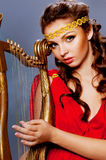 Moça bonita que joga a harpa Imagens de Stock Royalty Free