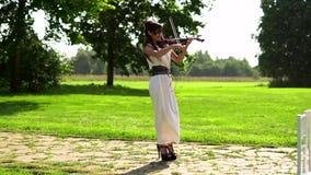 Moça bonita que joga no violino elétrico no parque bonito vídeos de arquivo