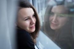 Moça bonita que olha fora da janela; vista do Fotografia de Stock Royalty Free