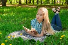 Moça bonita que pensa e que escreve em seu diário na grama com flores Front View imagem de stock royalty free