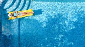 A moça bonita que relaxa na piscina, nadadas no colchão inflável e tem o divertimento na água em férias em família imagem de stock