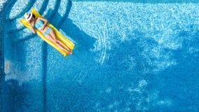 A moça bonita que relaxa na piscina, nadadas no colchão inflável e tem o divertimento na água em férias em família, vista aérea fotografia de stock royalty free