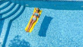 A moça bonita que relaxa na piscina, nadadas no colchão inflável e tem o divertimento na água em férias em família, vista aérea fotografia de stock