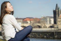 Moça bonita que relaxa próximo pelo rio e que olha para fora ao Fotos de Stock